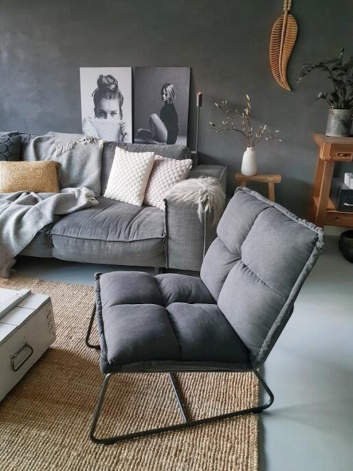 Woonkamer zithoek grijze bank stoel betonstuc